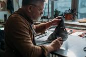 Fotografie Senior-Schuhmacher hält in Werkstatt Stücke aus echtem Leder