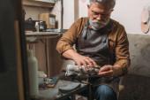selektivní zaměření starší vousaté obuvnické opravárenské obuvi v dílně
