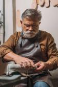 starší, vousatý švec v kožené zástěře opravárenská obuv v dílně