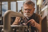 Selektiver Fokus des leitenden Schuhmachers nahe der Nähmaschine in der Werkstatt