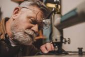Selektiver Fokus des bärtigen, älteren Schusters Nähleder auf Nähmaschine in der Werkstatt