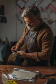 senior cobbler in apron holding piece of genuine leather in workshop
