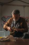 selective focus of senior cobbler holding piece of genuine leather in workshop