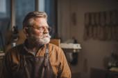 Fotografie selbstbewusster, älterer Schuster mit Brille, der in der Werkstatt wegschaut