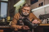 seriózní, senior obuvník držící koženou botu při pohledu na fotoaparát