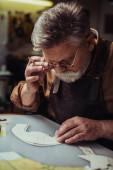 Aufmerksame Schuhmacherin berührt Brille beim Betrachten von Schablone in Werkstatt