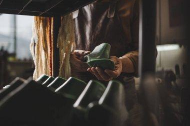 Partial view of cobbler holding shoe last in workshop stock vector