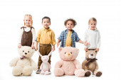 happy multicultural kids standing with teddy bears and bunny toy