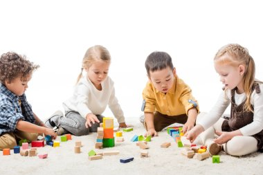 Cute multiethnic children playing with wooden blocks on carpet, isolated on white stock vector