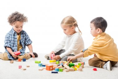 Multicultural kids playing with wooden blocks on carpet, isolated on white stock vector