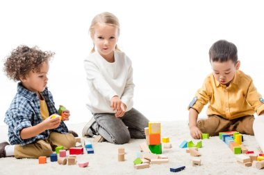 Multicultural children playing with wooden blocks on carpet, isolated on white stock vector