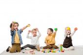 emocionální multikulturní děti hrající si s dřevěnými bloky na koberci, izolované na bílém