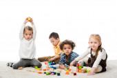 rozkošné multietnické děti hrající si s dřevěnými bloky na koberci, izolované na bílém