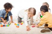 Fotografie multietnické děti hrající si s dřevěnými bloky na koberci, izolované na bílém