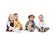 roztomilé multikulturní děti sedí spolu na bílém