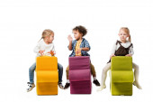 multiethnic children sitting on puzzle chairs, isolated on white