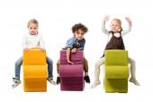 multikulturní děti sedící na skládacích židlích, izolované na bílém