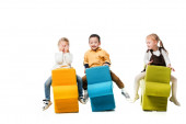 Fotografie cheerful multicultural kids sitting on puzzle chairs, isolated on white