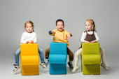happy multicultural kids sitting on puzzle chairs, on grey