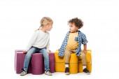 multikulturní podrážděné děti sedící na skládacích židlích, na bílém