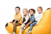 roztomilý multikulturní děti sedí na bin taška židle izolované na bílém