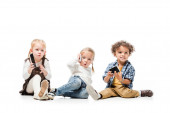 multicultural kids talking smartphones while sitting on white