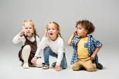 imádnivaló multikulturális gyerekek beszélő okostelefonok szürke