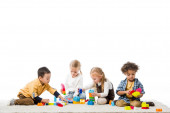 multikulturní děti hrající si s dřevěnými bloky na koberci, izolované na bílém