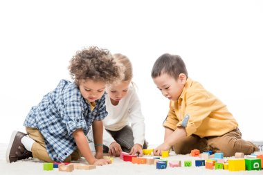 Multiethnic children playing with wooden blocks on carpet, isolated on white stock vector