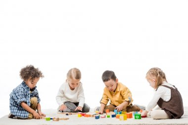 Multiethnic kids playing with wooden blocks on carpet, isolated on white stock vector