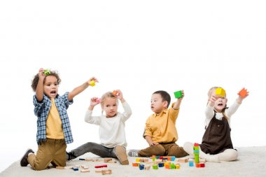 Emotional multicultural children playing with wooden blocks on carpet, isolated on white stock vector