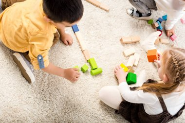 Top view of children playing with wooden blocks on carpet stock vector