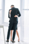 Photo back view of businessman in suit hugging secretary in office