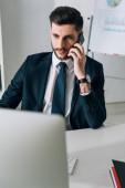 obchodník sedí u stolu a mluví na smartphone v kanceláři