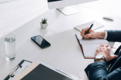 levágott kilátás üzletember ül az asztalnál, és írás a notebook