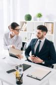 Fotografie attractive secretary showing folder to handsome businessman in office