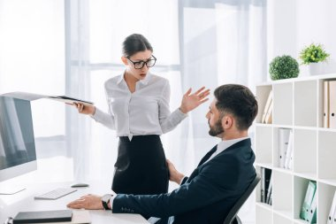 businessman touching butt of shocked secretary with folder in office