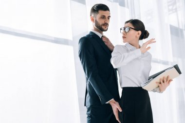 handsome businessman touching butt of shocked secretary in office