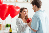 man holding heart-shaped gift box near happy girlfriend on valentines day