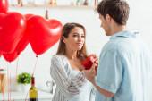 férfi gazdaság szív alakú ajándék doboz közelében boldog barátnő Valentin-napon
