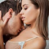 attraktives Mädchen mit großen Brüsten umarmt gutaussehenden Mann mit geschlossenen Augen
