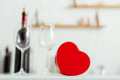 Photo selective focus of red heart-shaped gift box near empty glasses and bottle of wine