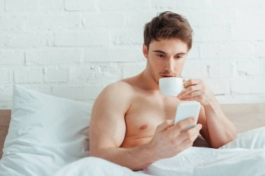 Handsome shirtless man holding cup of coffee while using smartphone in bed stock vector