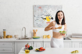 Beautiful sportswoman smiling at camera while holding bowl with salad near ripe vegetables and measuring tape on kitchen table