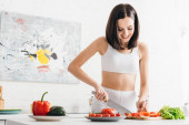 Smiling sportswoman cutting fresh vegetables and lettuce on kitchen table
