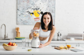 Selective focus of smiling sportswoman preparing smoothie near measuring tape and fruits on kitchen table, calorie counting diet