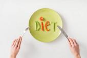 Horní pohled na ženu s příbory v blízkosti slovo dieta z rostlinných plátků na talíři na bílém pozadí