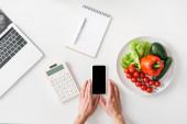Horní pohled na ženu držící smartphone v blízkosti kalkulačka, notebook a zelenina na bílém pozadí