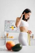 Selektiver Fokus einer lächelnden Sportlerin, die ihre Taille mit Klebeband in der Nähe von Früchten und einem Glas Wasser auf dem Küchentisch misst
