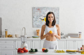 Smiling sportswoman holding orange near scales, measuring tape and vegetables on kitchen table, calorie counting diet